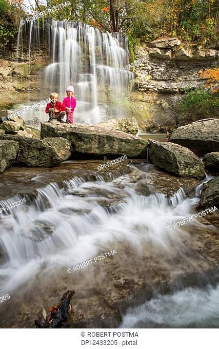 Brother and sister pose in front of a waterfall in Rock Glen Conservation Area; Ontario, Canada