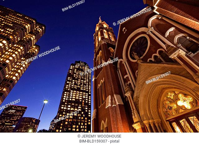 Low angle view of illuminated highrise buildings and Cathedral Santuario de Guadalupe, Dallas, Texas, United States