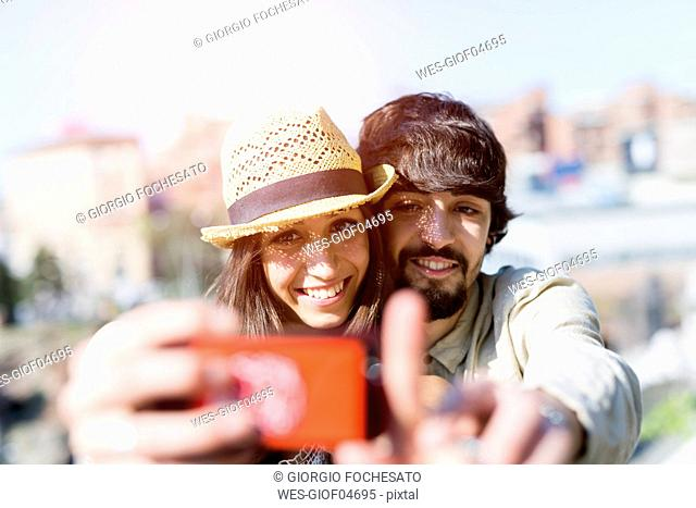 Portrait of happy young couple taking selfie with smartphone