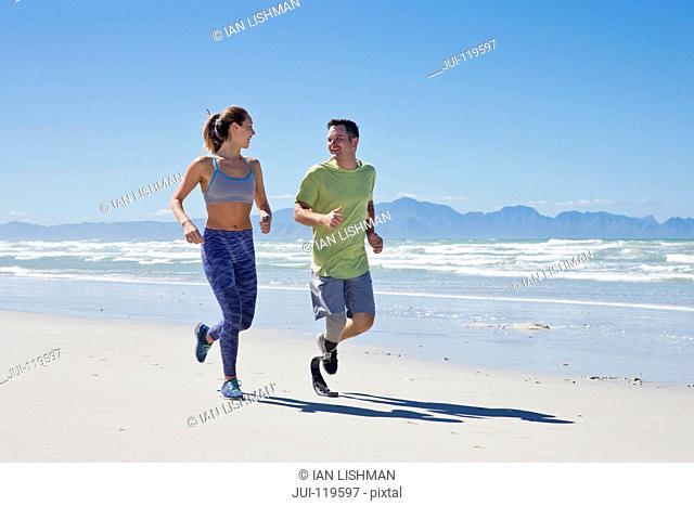 Man Wearing Prosthetic Blade Running Along Shoreline Of Beach With Female Partner