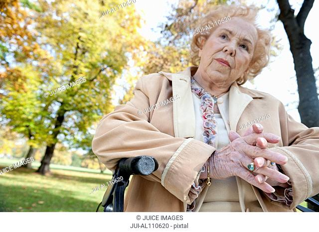 Senior woman with hands clasped in park