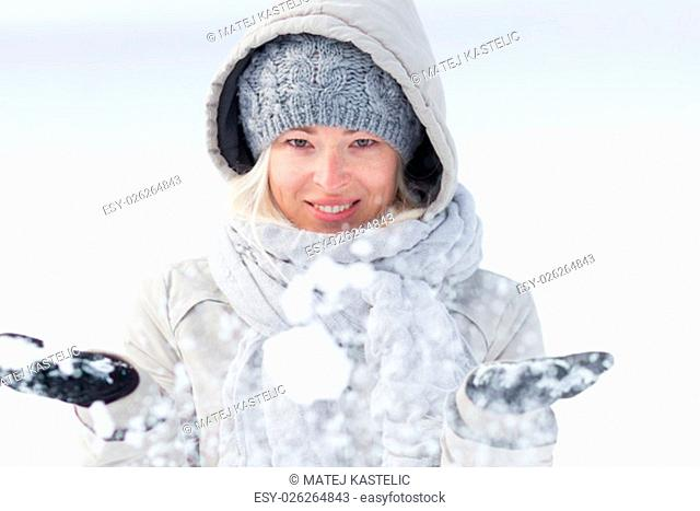 Cute casual young woman playing with snow in winter time