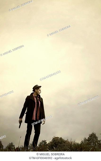 Man Standing in Field with Gun