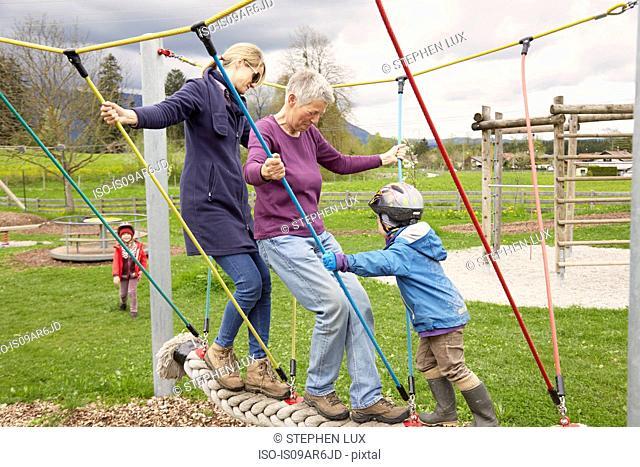 Three generation family playing on rope bridge