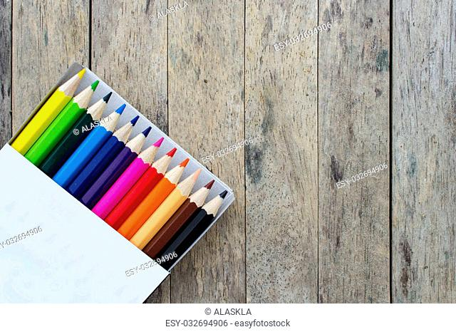 color pencils in a box on wood plank background