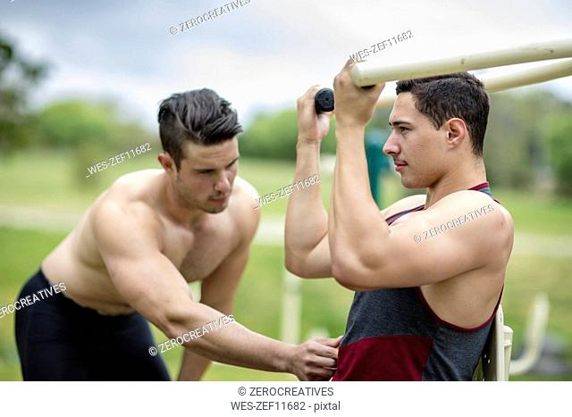 Two young men doing strength training in park