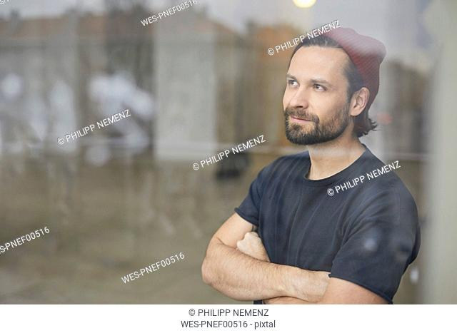 Portrait of an artist in his atelier looking out of wondow