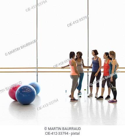 Women talking at barre in exercise class gym studio