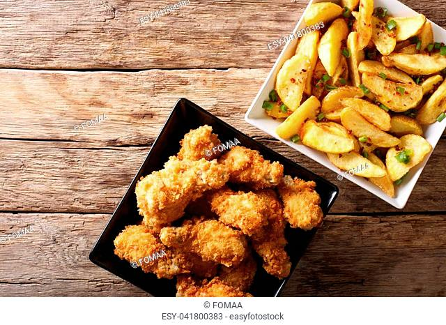 Fried chicken wings in bread crumbs and potato wedges close up on the table. horizontal top view from above