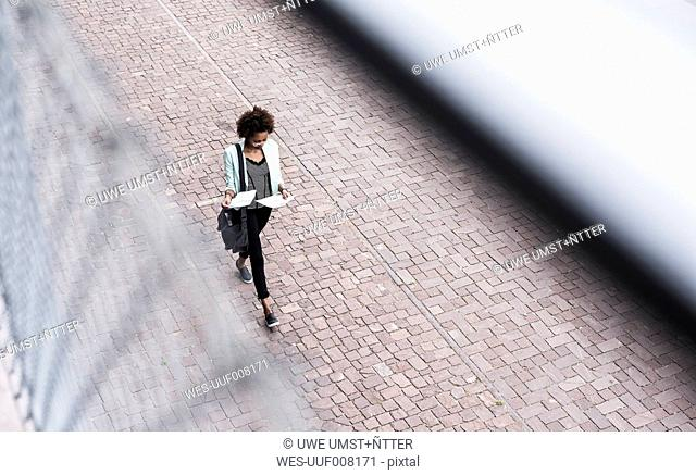Walking businesswoman looking at documents, seen from above