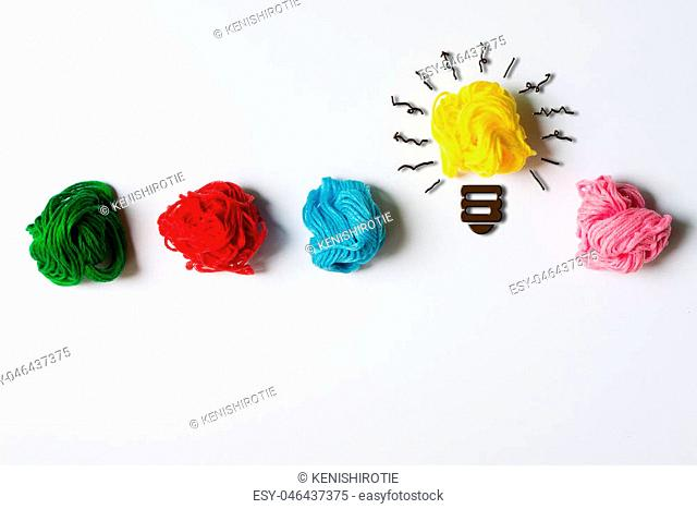 Light bulb in a row of multicolor yarn balls over white background