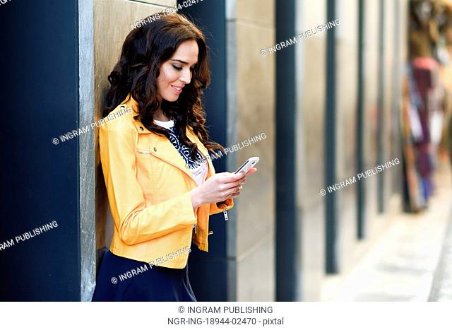 Young brunette woman, model of fashion, wearing orange modern jacket and blue skirt, texting with her smartphone in urban background