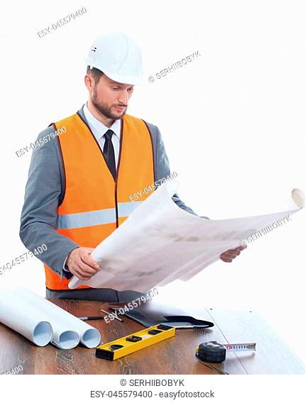 Engineer wearing in orange vest, suite and white safety hat holding big drawing plan. Male with beard reading architecture plan of building