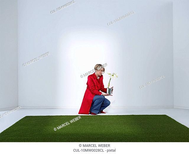 Women looking at flower in green office
