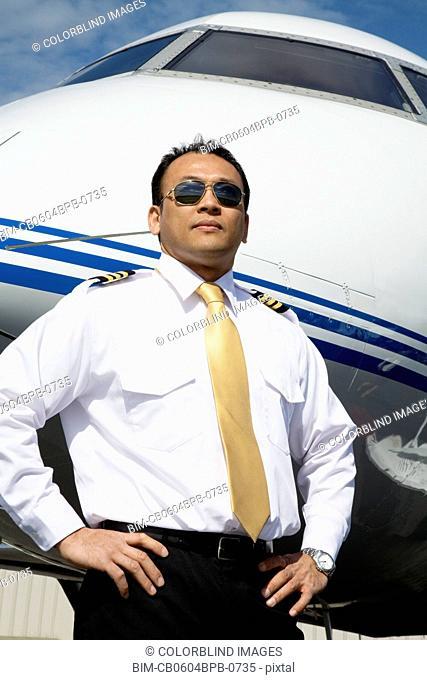 Asian male pilot standing near airplane