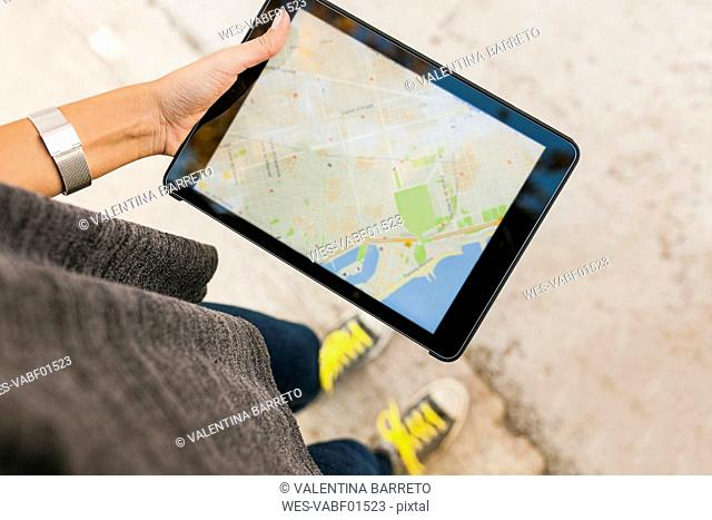Close-up of woman holding tablet with digital street map