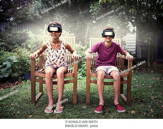 Mixed race children watching virtual reality screens