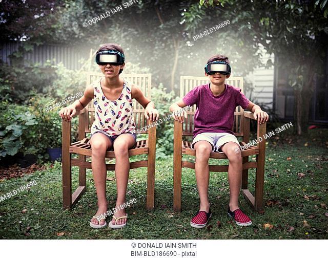 Mixed race children watching virtual reality screens