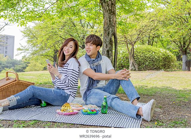 Young smiling couple having a picnic at park in spring