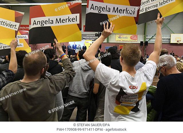 CDUsupporters hold up posters, Angela Merkel speaks in the background, during a CDU election campaign event in Wolgast, Germany, 08 September 2017