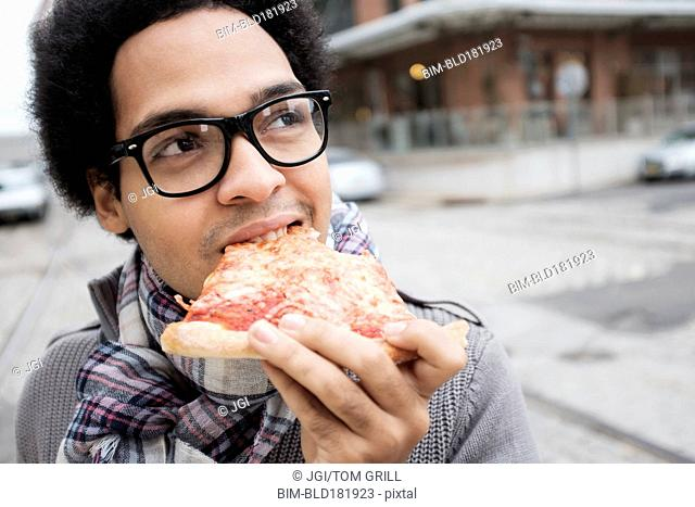 Mixed race man eating pizza outdoors