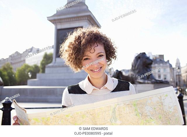 Portrait of smiling woman holding map in London