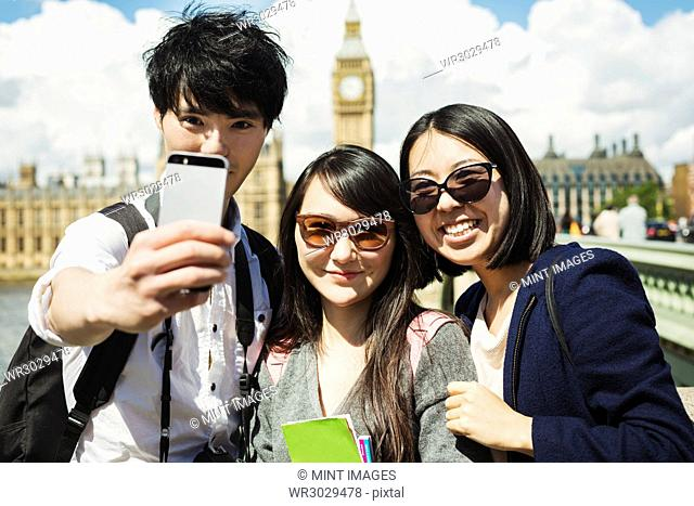 Smiling man and two women with black hair taking selfie with smartphone, standing on Westminster Bridge over the River Thames, London