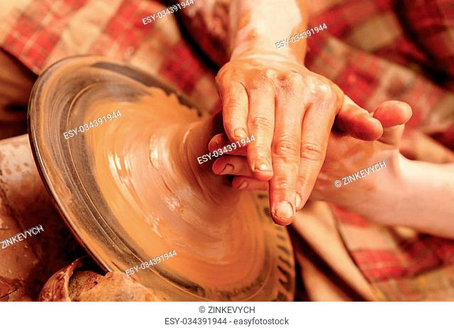 Creation of a clay pot. Close-up of hands of a teacher and a student working on pottery wheel and creating a clay pot