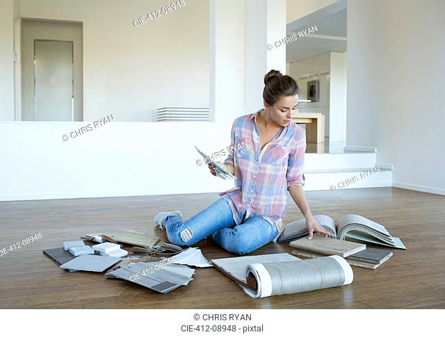 Woman viewing carpet and tile swatches on floor in new house