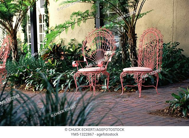 Two pink ornate wrought iron chairs on tropical patio