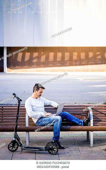 Casual businessman with kick scooter, sitting on a bench, working relaxed in the city