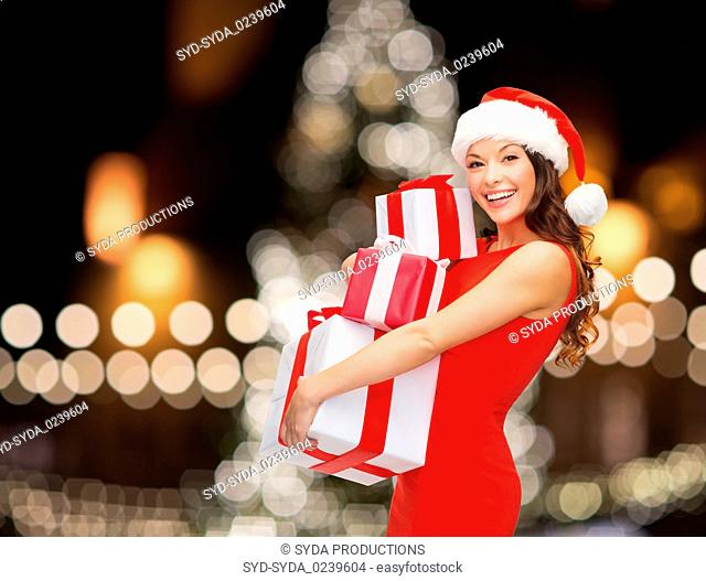 smiling woman in santa hat with gift boxes