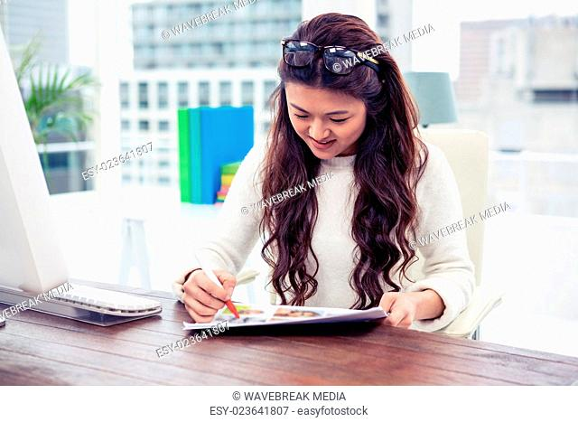 Smiling Asian woman looking at documents