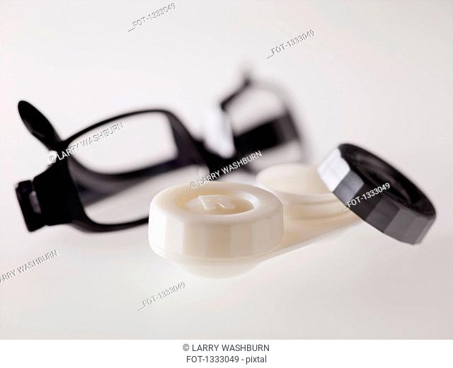 Contact lens case and glasses over gray background