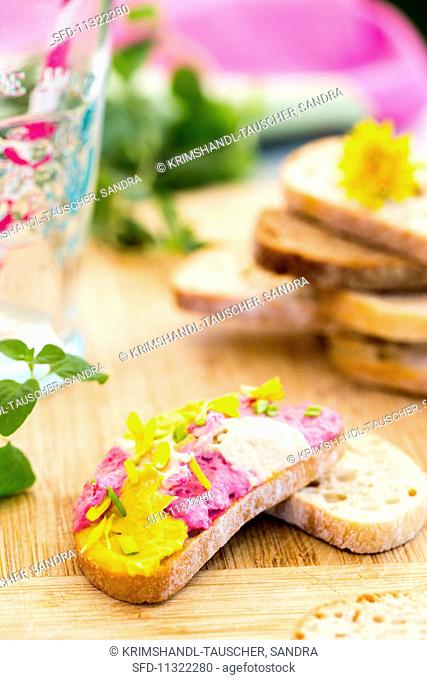 A slice of bread topped witj hummus, marigold petals and onions