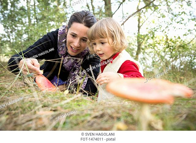 Mother and daughter exploring mushroom on field