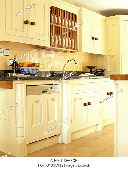 Fitted dishwasher below wall-cupboard with integral plate-rack in cream kitchen painted in Farrow+Ball paint