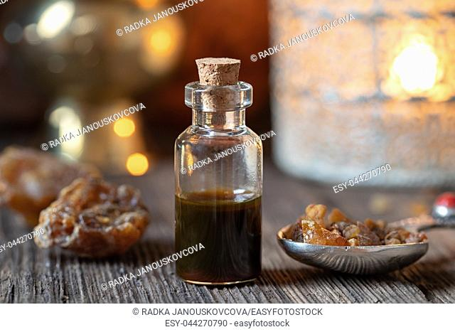 A bottle of essential oil with myrrh resin on a spoon