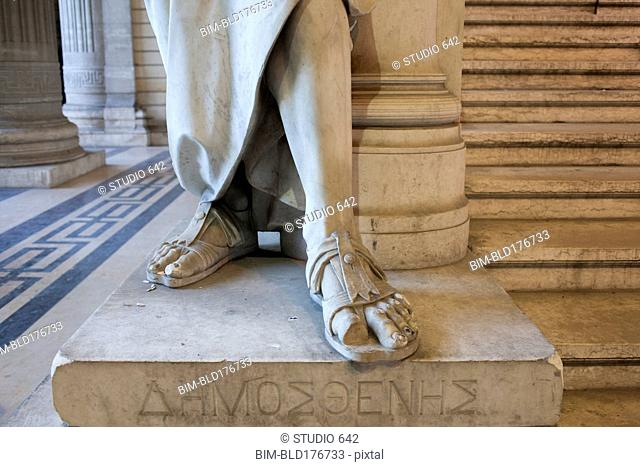 Close up of feet of carved statue on marble pedestal
