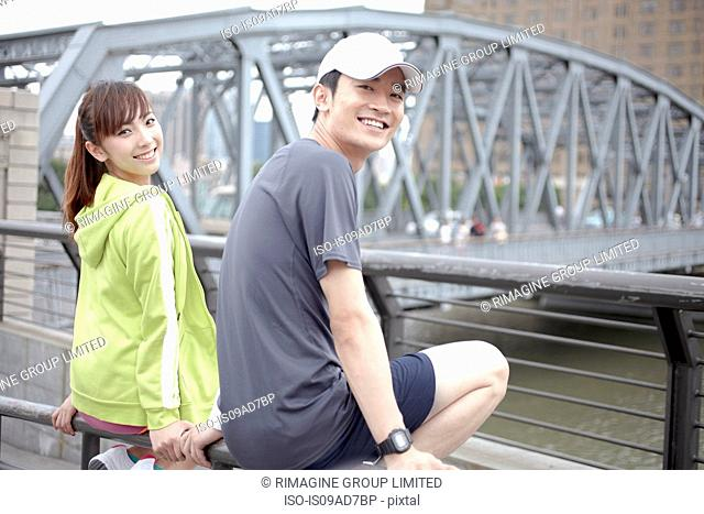 Male and female joggers sitting by bridge