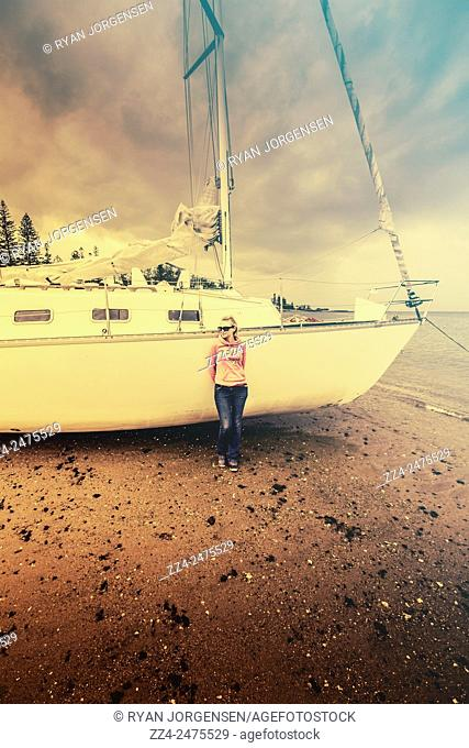 Image with retro filter of a full length young woman in twenties relaxing when leaning on a sail boat. . Stormy day retreat
