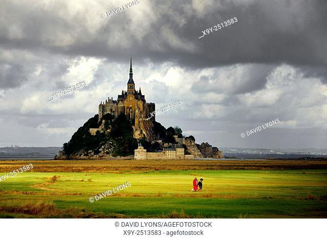 Normandy France. Le Mont Saint Michel. East across the tidal bay salt marsh. Man woman dog walking in evening light