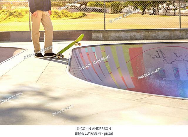Caucasian man standing on skateboard in skate park