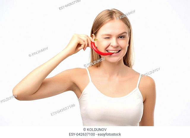 Female mouth holding red hot chili pepper. She likes spicy taste. Ingredient for fat-burning diet