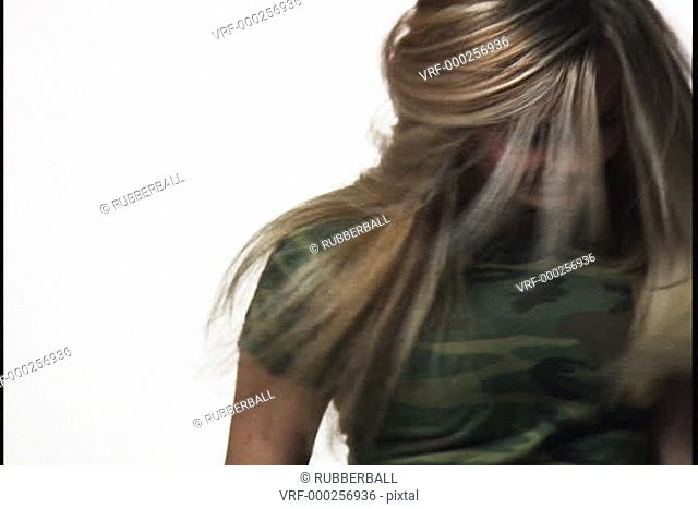 close up of a blonde teenage girl as she playfully dances and tosses her hair around