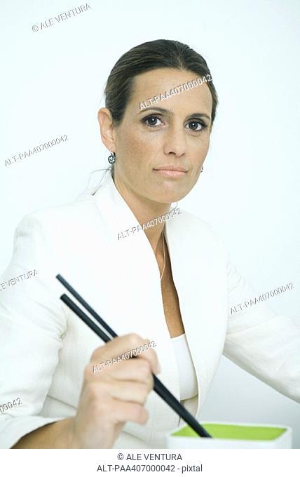 Businesswoman holding chopsticks, portrait