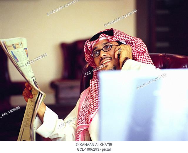 Saudi businessman reading Arabic newspaper and using mobile phone