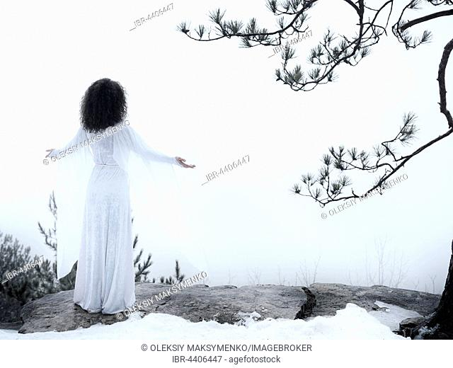 Woman in white dress standing on a cliff, meditating with spread hands, embracing the nature, spiritual concept, wintertime outdoor scenery