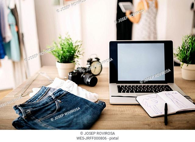 Laptop, clothes and sketchbook on desk with woman in background