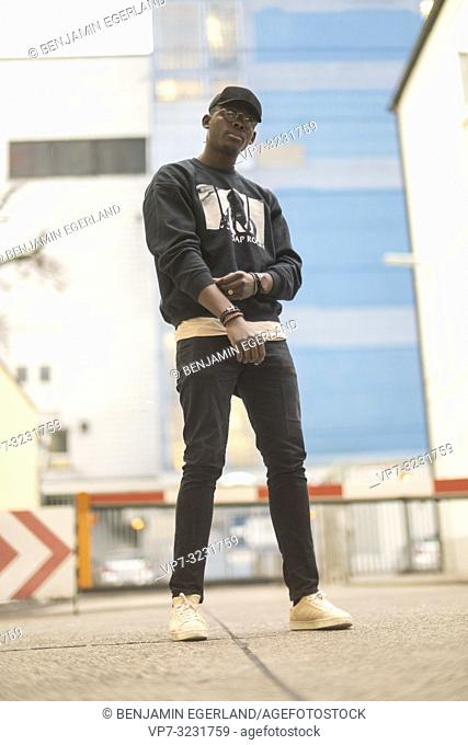 man wearing urban men's fashion street style clothes, at industrial area in Munich, Germany